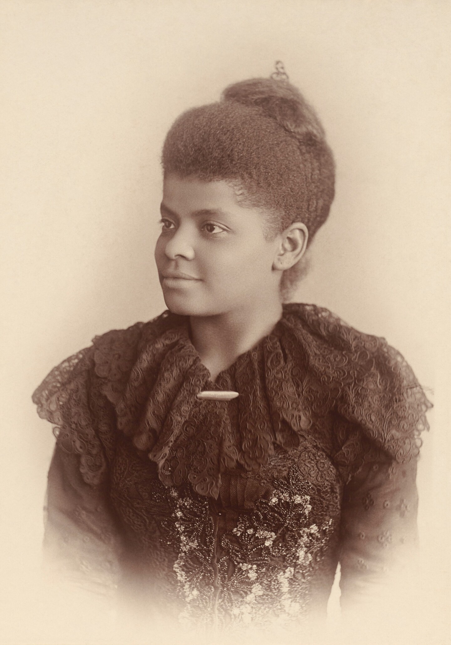 A sepia portrait of Ida B. Wells where she is wearing a piece of clothing with a frilly neckline. Her hair sits atop her head.