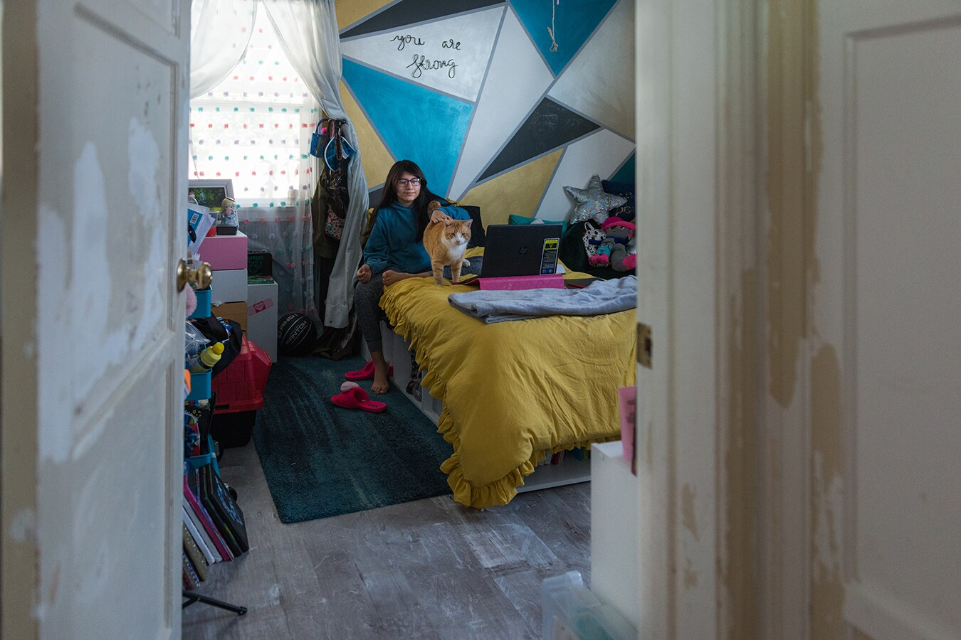Rhianna plays with her cat in her bedroom. She's sitting on a mustard yellow blanket with a laptop on her bed. Behind her is a geometric painted wall with triangles painted in various blues and yellow.