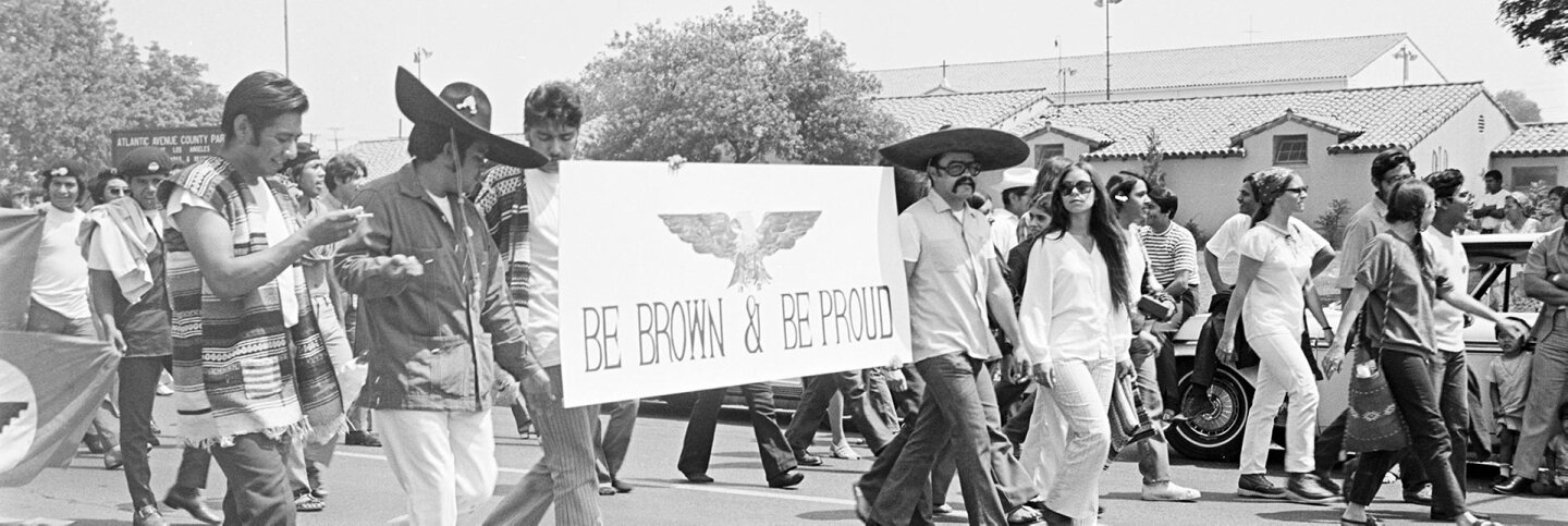 """CSRC_LaRaza_B4F4C4_Staff_001 Protesters march on Whittier Boulevard with the sign """"Be Brown & Be Proud"""" 