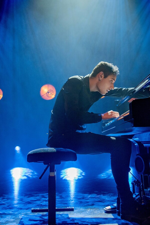 "Peter Bence in the middle of a piano performance on stage. | From ""Peter Bence: Around the World"""