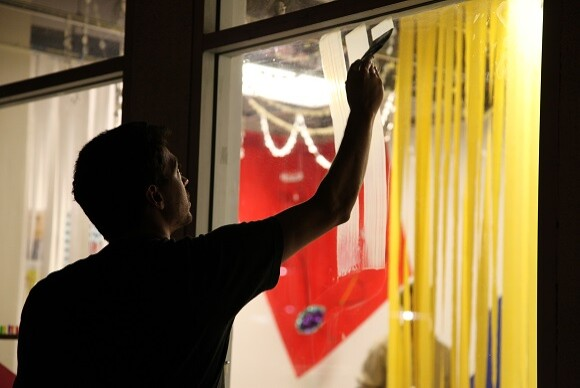 Artist Michael Dopp paints the exterior windows of Actual Size as part of 3, a party environment with contributions from over 20 Artists to celebrate Actual Size's third Anniversary. | Photo courtesy Corrie Siegel.