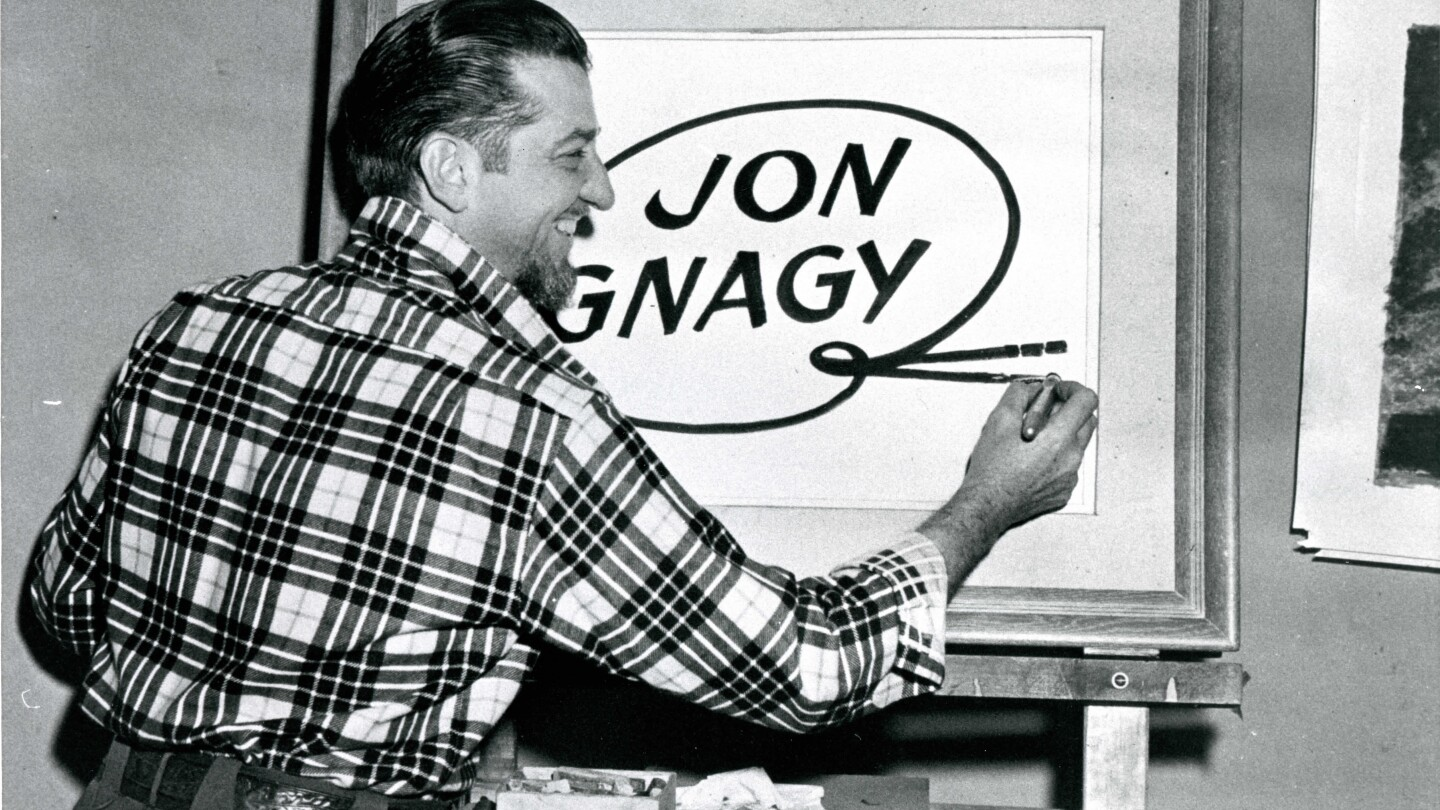 Jon Gnagy signs his name on an easel with his back turned to the camera. The profile of his face can be seen and he is wearing a plaid collared shirt.