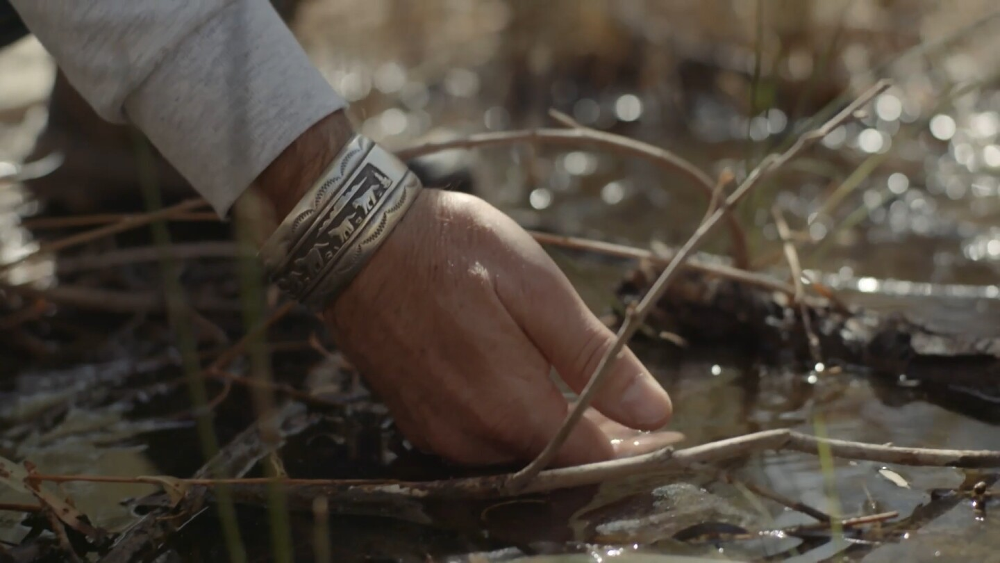 "A person's hand dips into shallow water. | Still from ""Tending Nature: S3 E2 - Preserving the Desert with NALC"""
