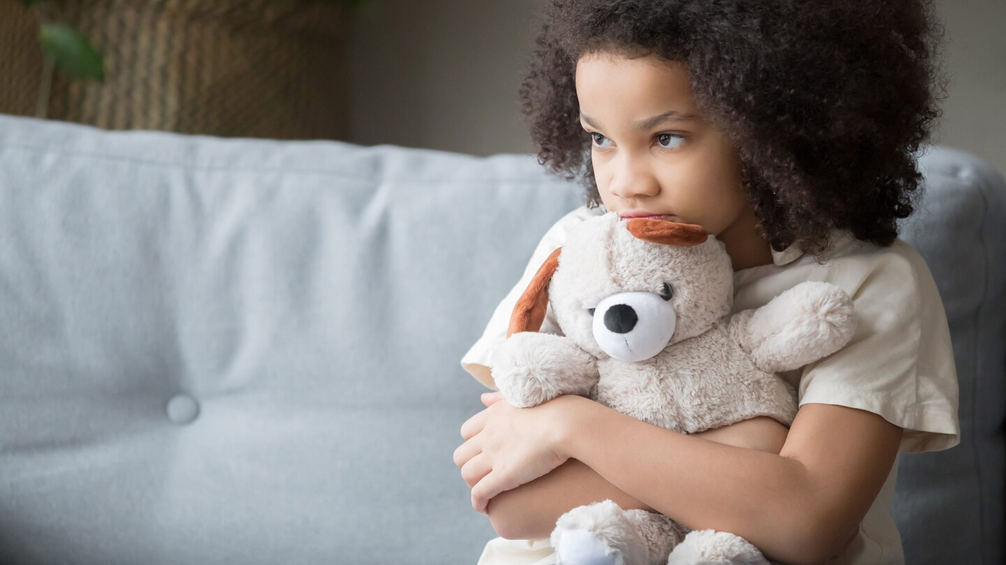 Upset looking little girl holds a teddy bear tightly and looks away at the camera as she sits on a couch.