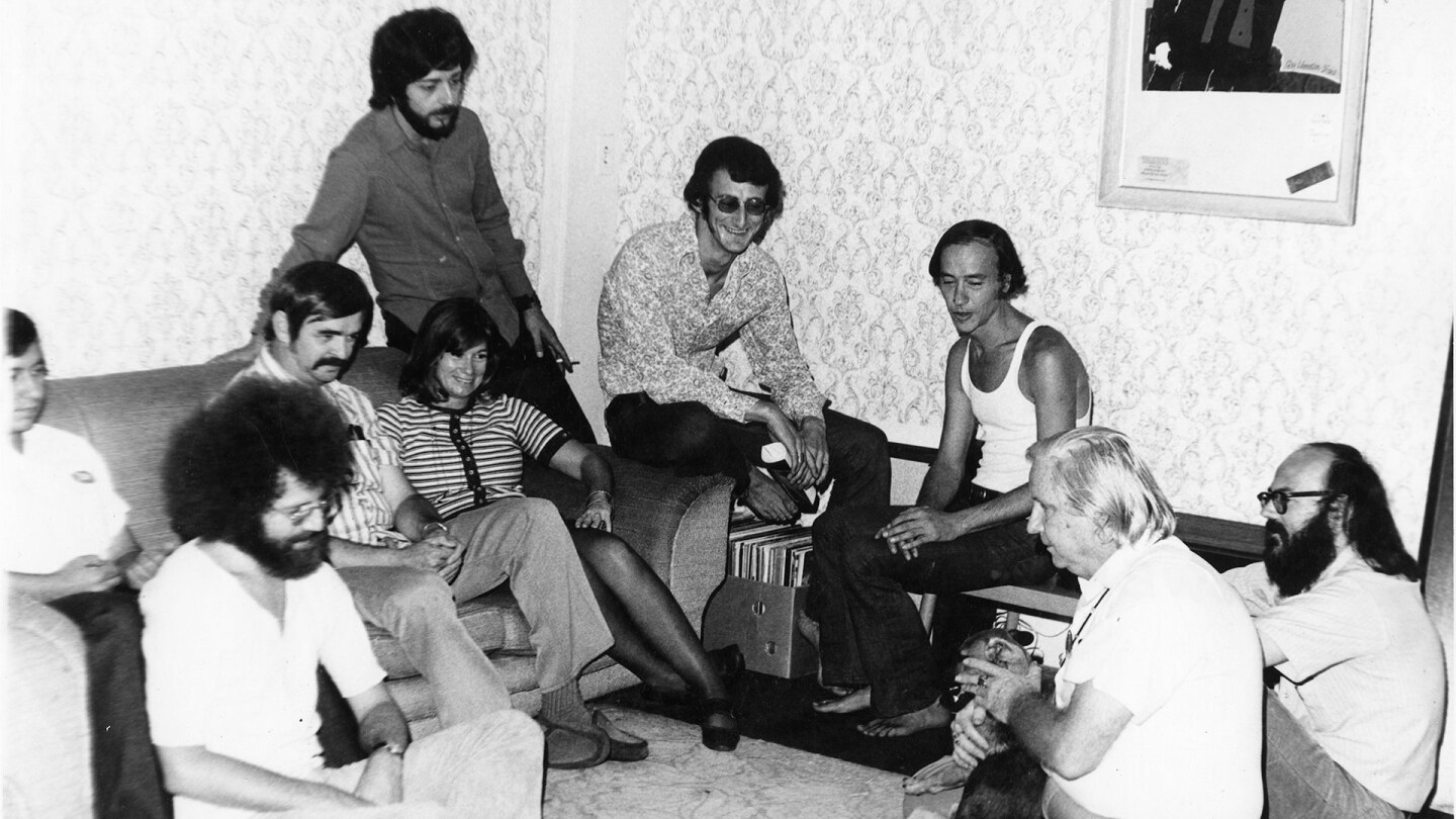 Left to right: John Platonia, Jim Kepner (moustache), Howard Fox (standing), June Herrle, Jim-Ed Thompson, Ralph Schaeffer, Morris Kight, Don Kilhefner (far right) and another person at the Gay Community Services Center, 1971. | Pat Rocco/USC Libraries