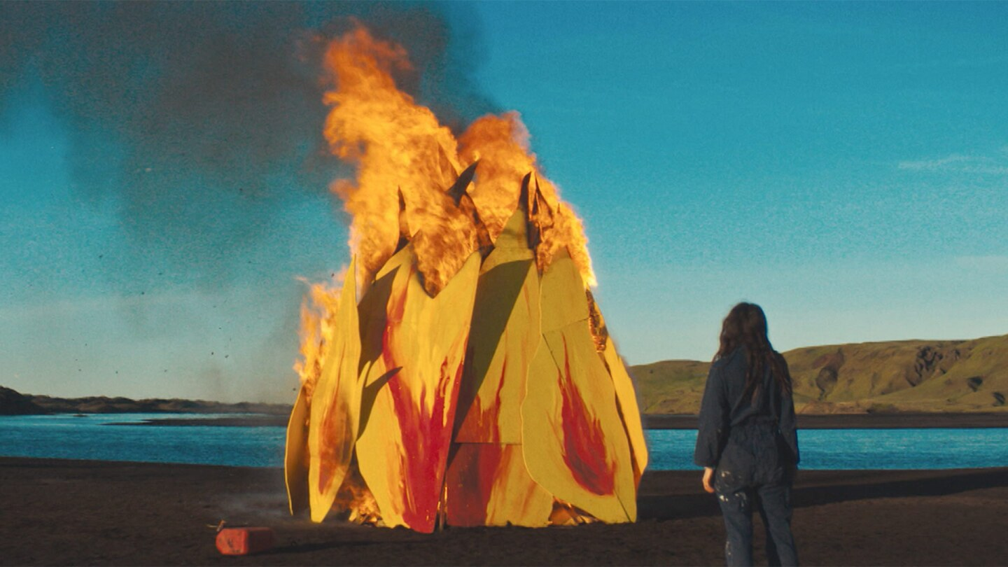 Still from Forever Love: A woman stands next to a fire in front of a lake.