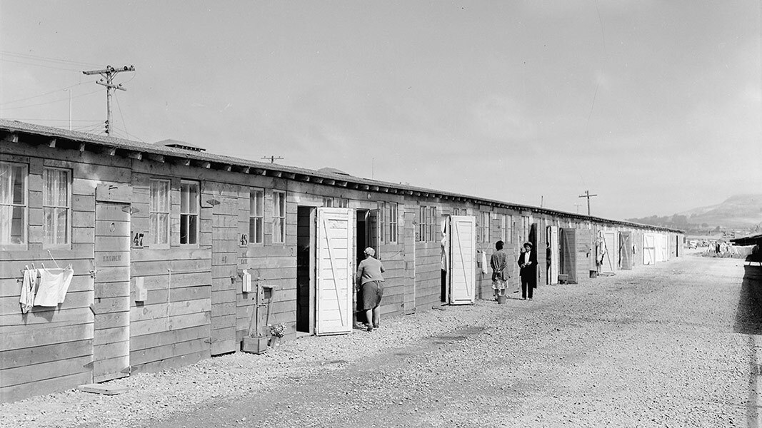 Black and white photo of low wood barracks at a Japanese internment camp