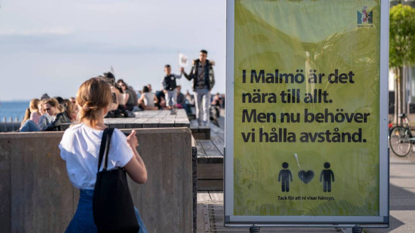 "People enjoy the warm evening at Sundspromenaden as the sign reads ""In Malmo everything is near. But now we need to keep a distance"" in Malmo, Sweden May 26, 2020. TT News Agency/Johan Nilsson via REUTERS"
