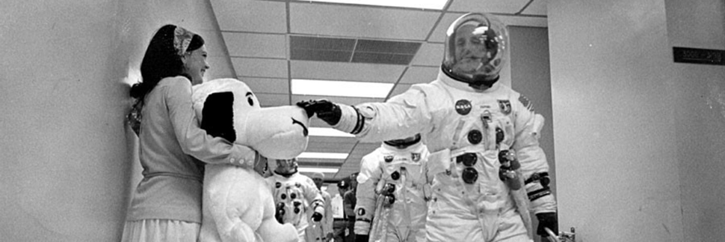 Thomas P. Stafford petting Snoopy as Jayme Flowers Coplin holds him. | NASA