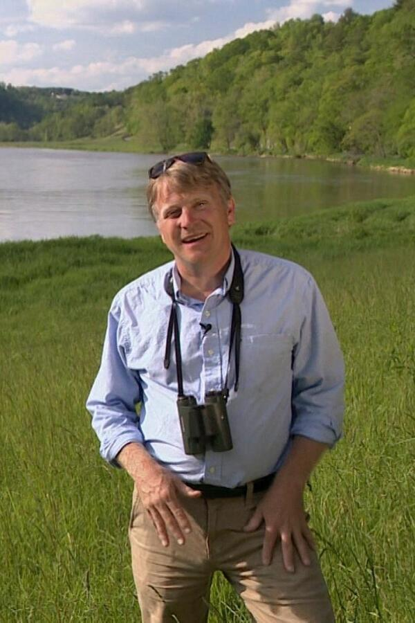 "Patrick McMillan stands in a grass field alongside a river. | From ""Expeditions with Patrick McMillan"""