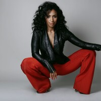 Chloe Arnold is photographed professionally wearing a leather-like top and red pants.
