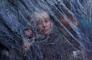 Rain drops are seen on outdoor protective plastic sheeting surrounding a woman at a cafe in Galway, Ireland, October 20, 2020. | REUTERS/Clodagh Kilcoyne