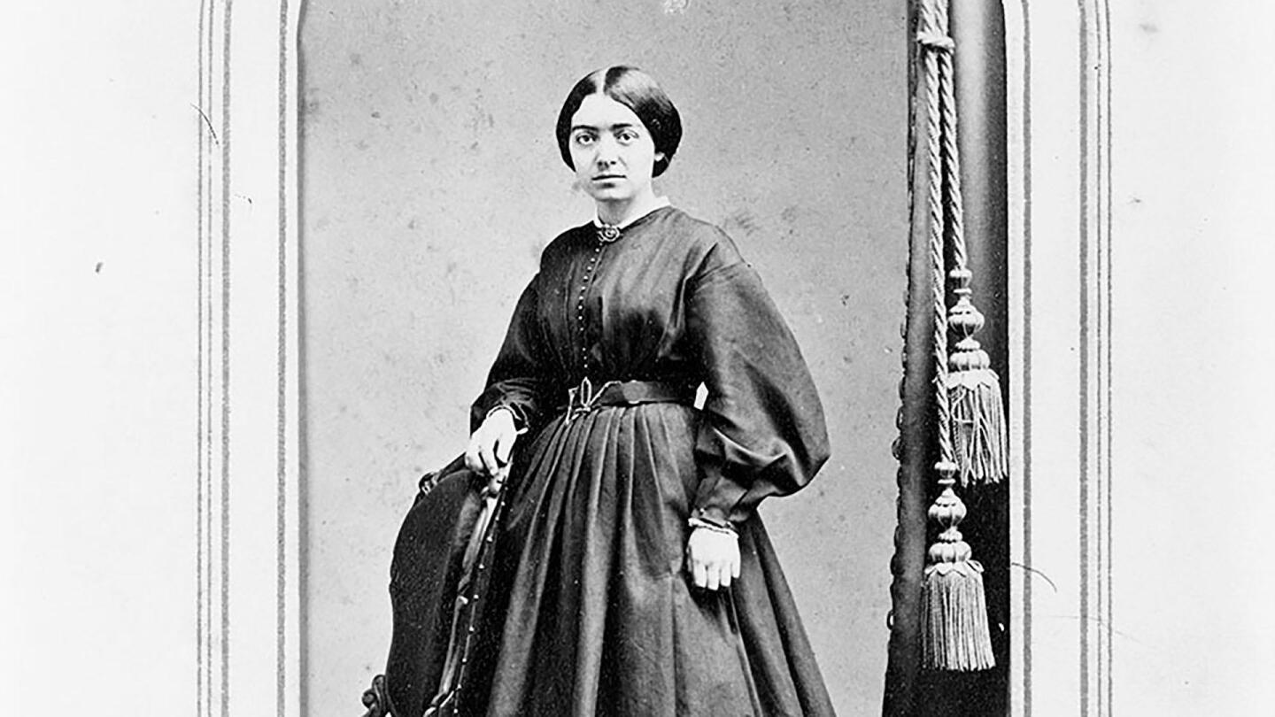 """A woman poses behind a chair for a photo. 