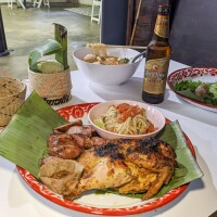 A table is prepared with various Lao dishes. The plate in the foreground is a papaya salad with Lao sausage and chicken. Behind it is a bowl of sukiyaki. To the left of the papaya salad is sticky rice nestled in a small woven basket and to the right is a plate of sakoo yut sai or tapioca dumplings. A bottle of beer also sits on the table.