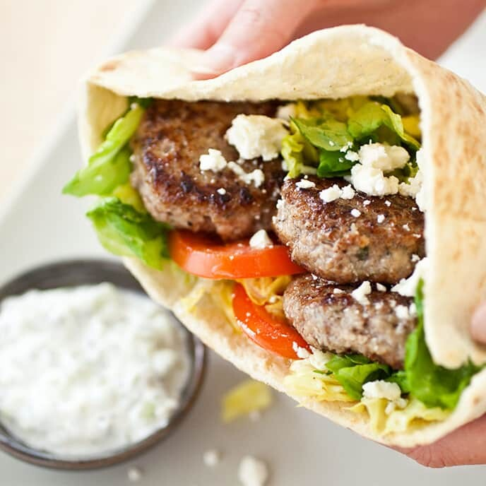 A pita sandwich filled with tomatoes, small clumps of feta cheese, lettuce and small patties of meat, with a white sauce in the background.