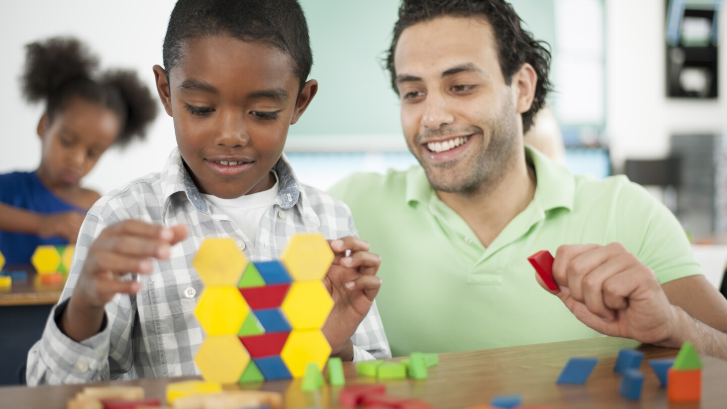 A teacher is helping a student with stacking blocks sorted by color in class.