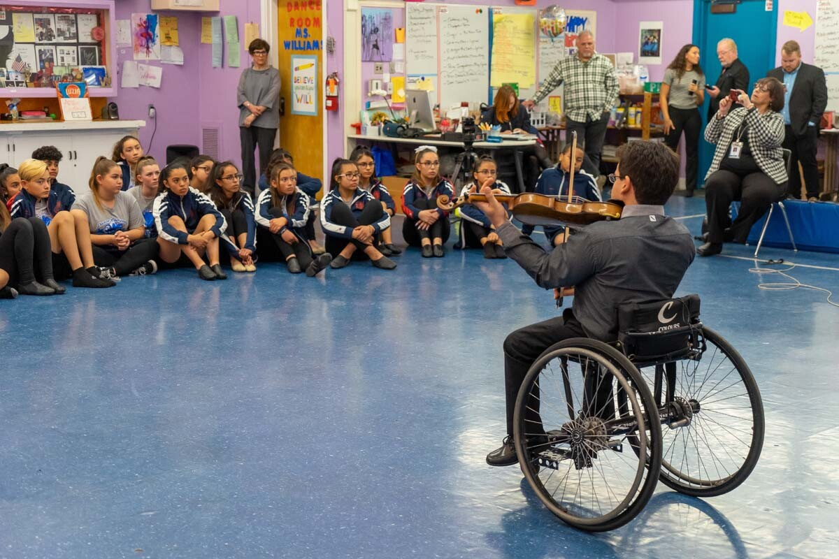 Artist-in-residence and violinist Niv Ashkenazi performs seated on his wheelchair for seated children in front of him at one of The Soraya's Violins of Hope concerts for arts education at Patrick Henry Middle School in Granada Hills, California on Dec. 5,