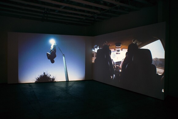 """Installation shot of Kahlil Joseph's """"m.A.A.d,"""" featured in exhibition """"The Oracle,"""" curated by Noah Davis, at the Underground Museum. 2014. 
