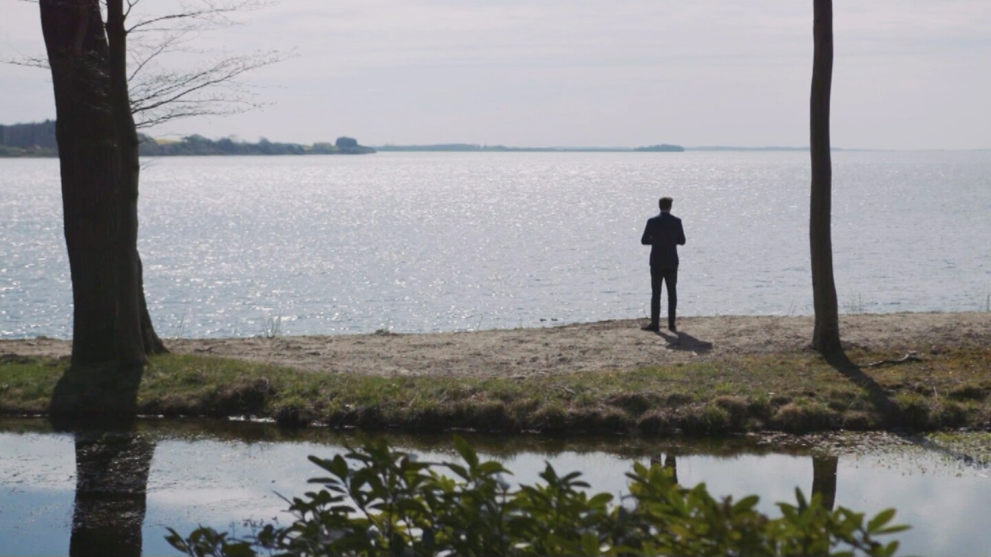 """A man stands beside a vast lake. 