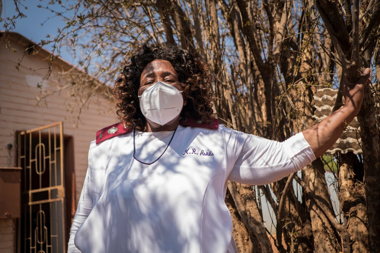 Sister Rachel Asitile (61) stands for a portrait outside the home of a patient who tested positive for COVID-19. | Thomson Reuters Foundation/Gulshan Khan