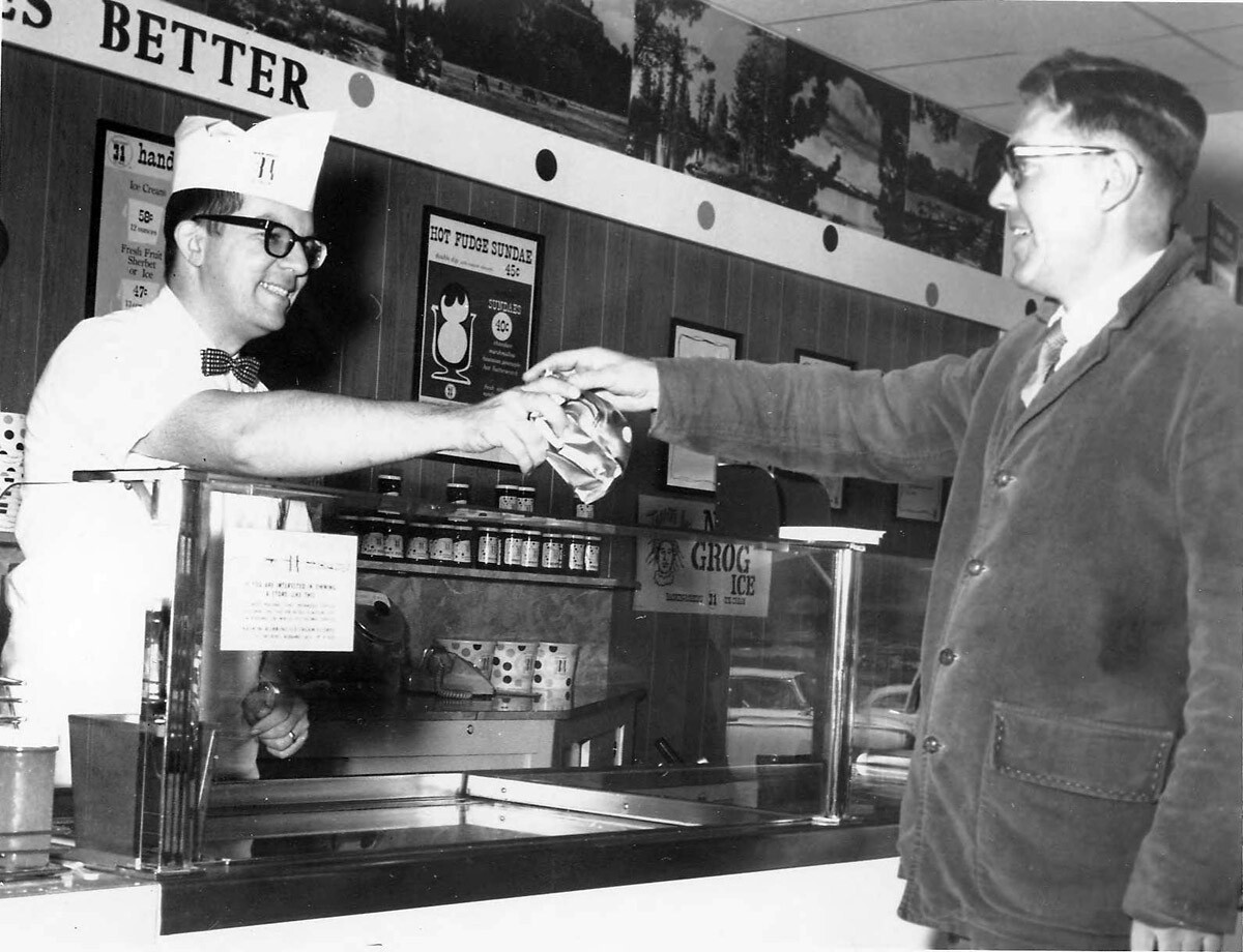 Wayne Holmberg, left, hands Olaf Pahn, Newbury Park, a serving of one of Baskin-Robbins 31 flavors at Conejo Village Shopping Center. May 3, 1967. | Thousand Oaks Library