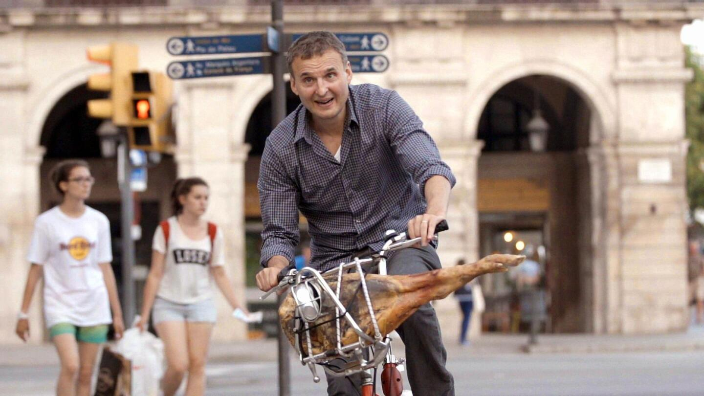 Phil Rosenthal riding a bike with the leg of an animal strapped onto it.