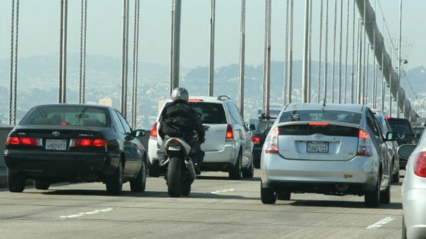 A motorcyclist lane splits on the Bay Bridge in San Francisco.