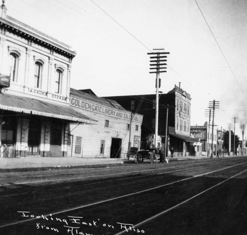 The French district in Los Angeles is shown looking east on Aliso Street from Alameda Street. The photo includes a French bakery and the Golden Gate Livery and Sale Stables are shown.