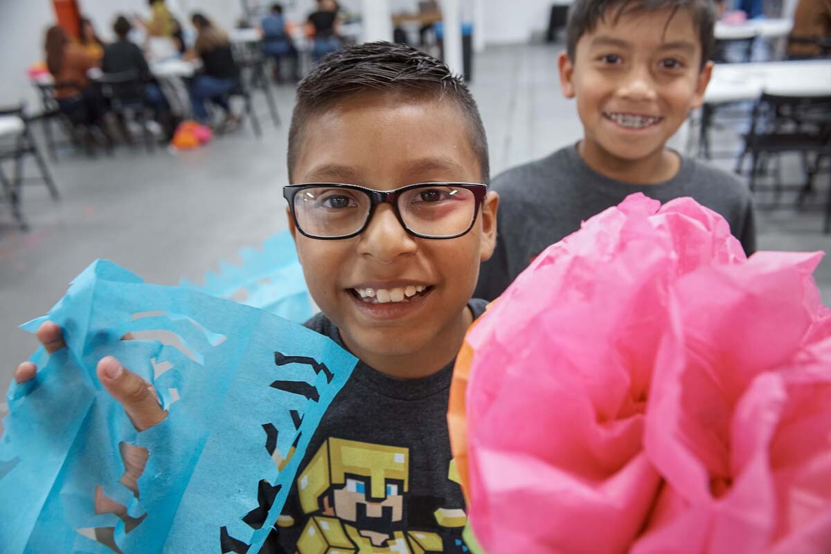 A young boy holds up blue papel picado and a pink paper flower at Self Help Graphics' Dia de los Muertos season of workshops, 2019. | Ken Marchionno