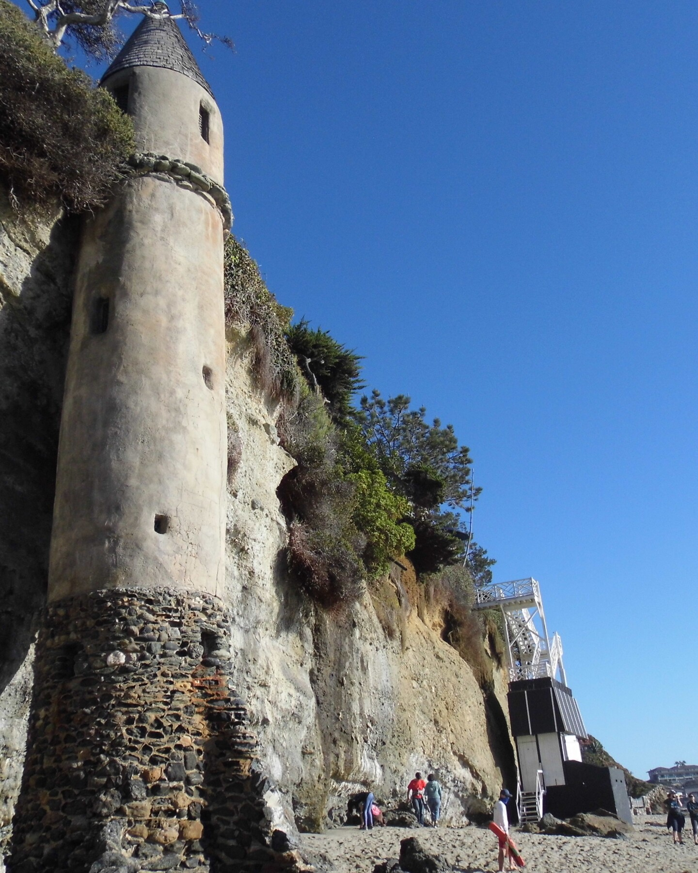 Locals walk along the coast of Victoria Beach as the medieval looking tower stands over them.