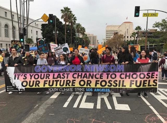 "A group of people hold a banner that reads ""Governor Newsom it's your last chance to choose: our future or fossil fuels"" at a Youth Climate Strike Los Angeles march in December 2019."