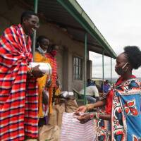 Nelson Ole Reiyia, founder of the Nashulai Maasai Conservancy,  distributes food rations to community members at the conservancy located near the Maasai Mara National Reserve in Narok county, Kenya on July 14, 2020. |THOMSON REUTERS FOUNDATION/Nita Bhalla