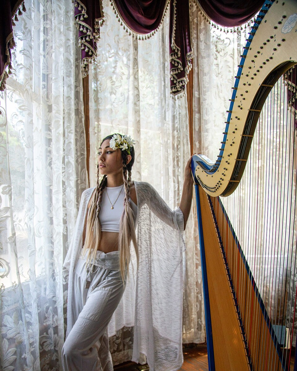 Low Leaf poses next to her harp inside the Perry House at Heritage Square Museum. | Azul Amaral