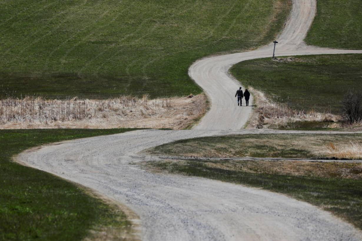 Two people walk along a gravel road amid the coronavirus disease (COVID-19) outbreak in Sabattus, Maine, U.S., April 25, 2020.   REUTERS/Brian Snyder