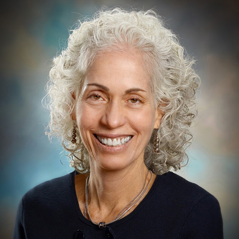 Barbara Ferrer smiles wearing a black top and her signature white curly hair.