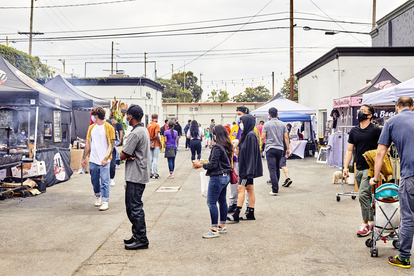 Attendees peruse and wait in line in between booths and tents at the FilLed Market, an outdoor market filled with curated Filipino American food and goods.