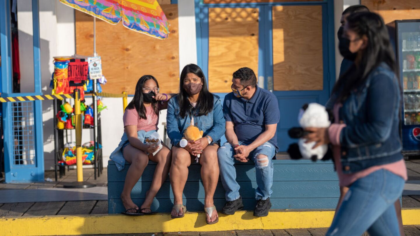 A family wearing masks sits on a bench at the Santa Monica Pier amid the coronavirus pandemic on April 20, 2021 in Los Angeles, California.