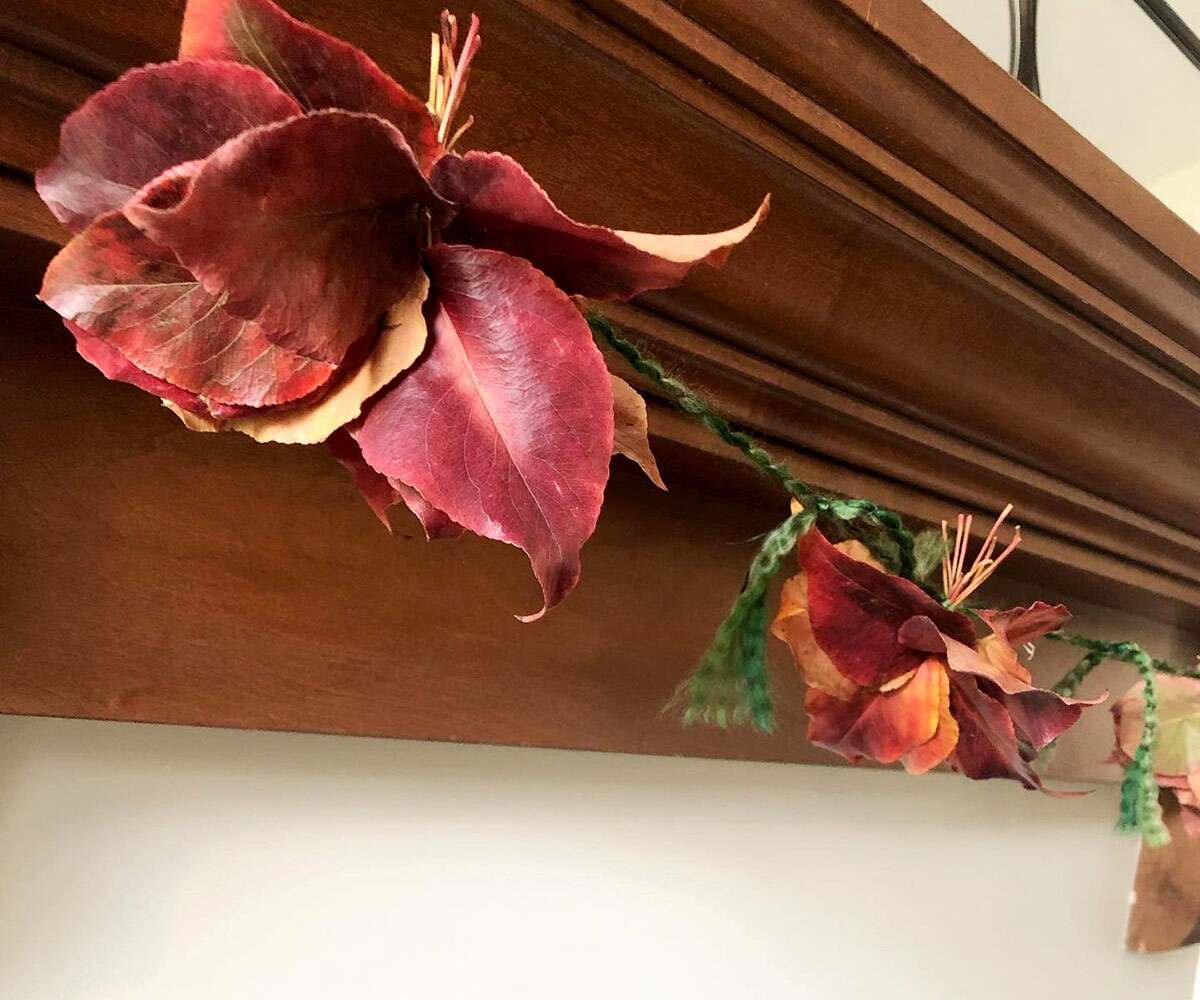 Close up shot of a garland made of fall leaves as it hangs off a mantle.