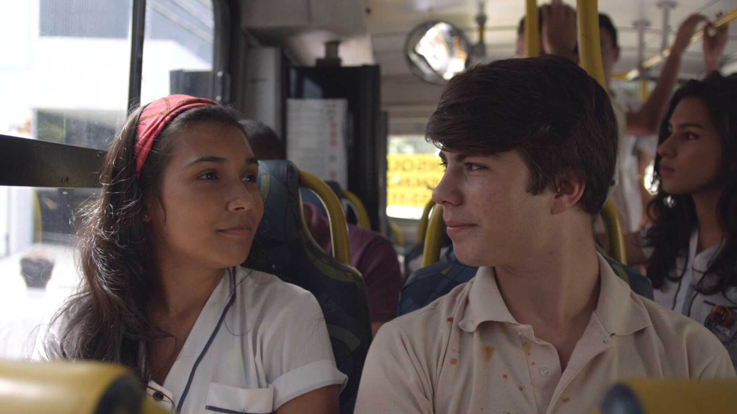 "A young woman and a young man sit next to each other on a bus. | Still from ""Casa Grande"""