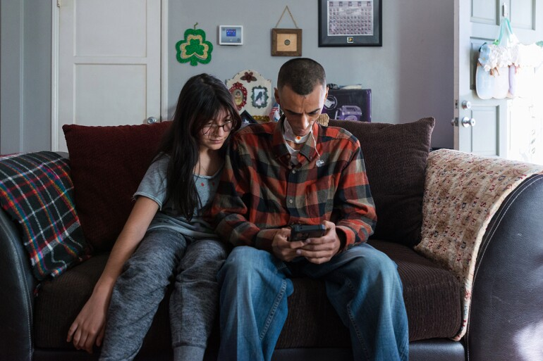 Rhianna sits next to her father on the couch, looking over at his phone.