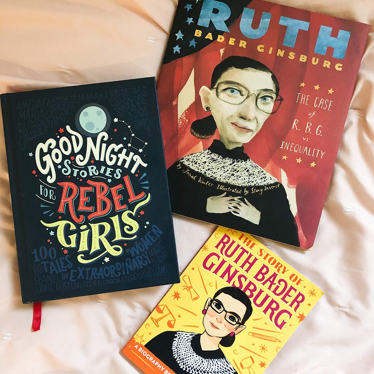 Three colorful children's book featuring historic women and/or Justice Ruth Bader Ginsburg lie on a cream colored sheet.