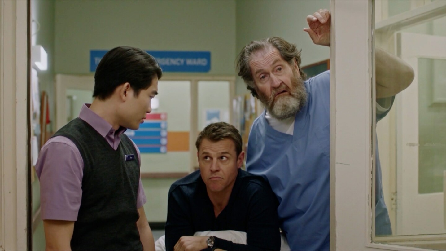Three men linger by a doorway in a hospital.