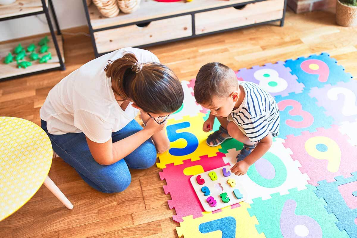 An adult engages with a child playing on a number mat.