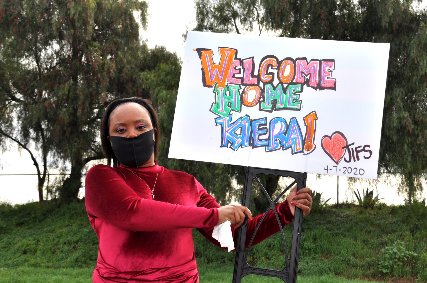 Kiera Newsome poses with her welcome home sign, wearing a protective face mask from her family | Gina Pollack