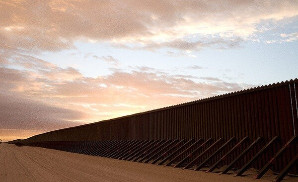 The border fence at the Imperial Sand Dunes in California