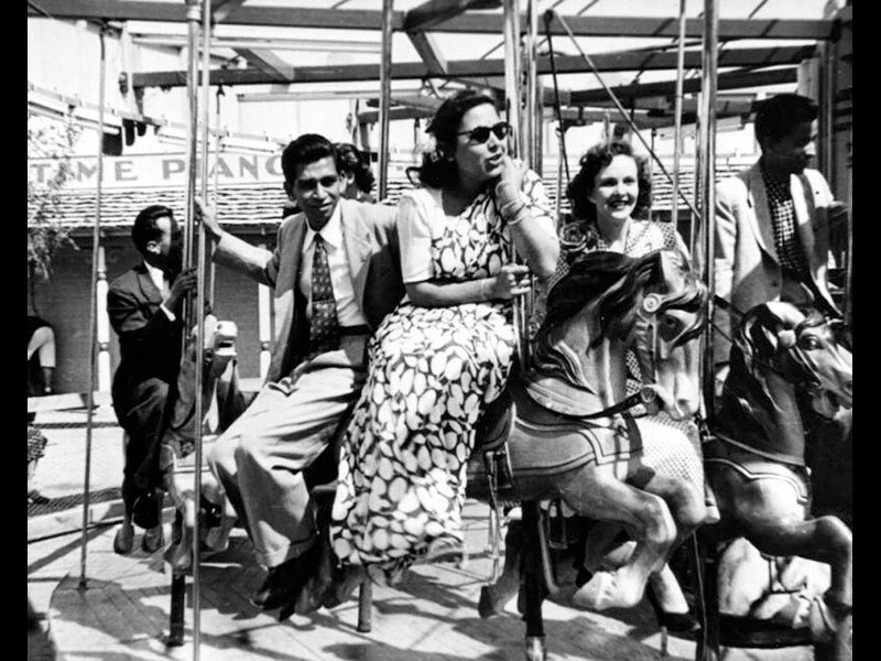 Black and white photo of a man in a suit riding a carousel with two women, one in a sari.