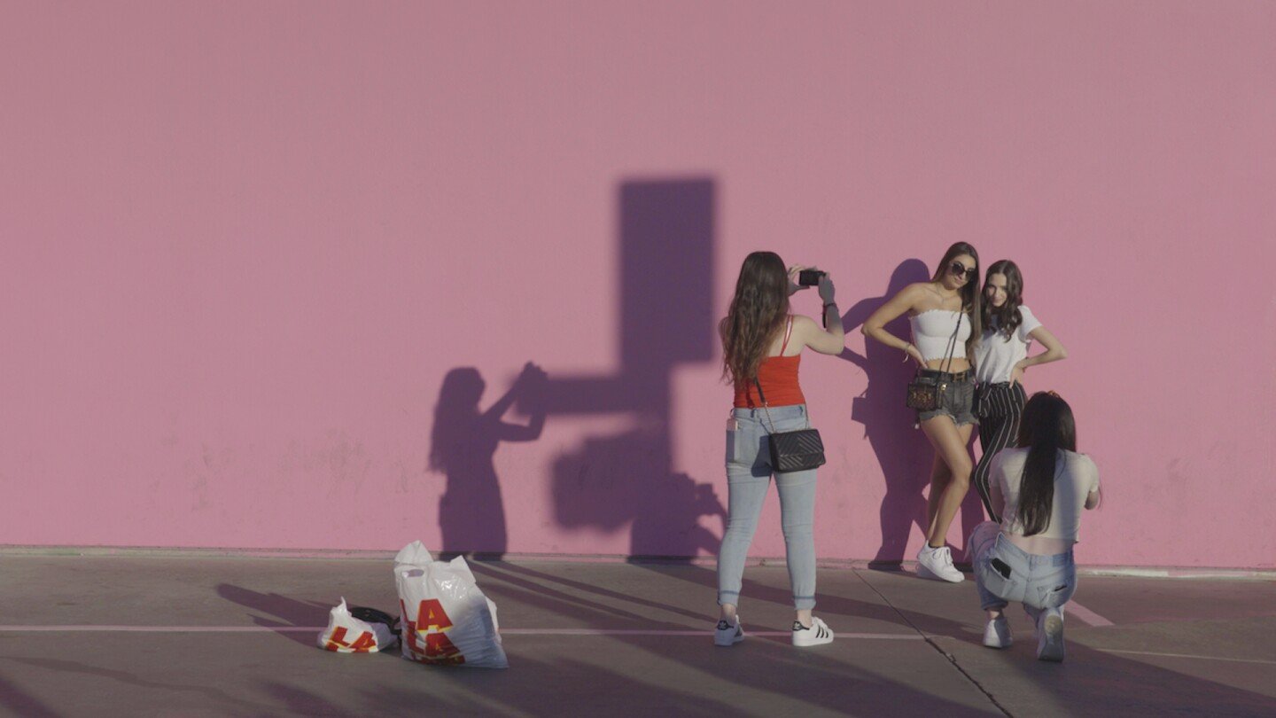 Girls take photo with Pink Wall in LA