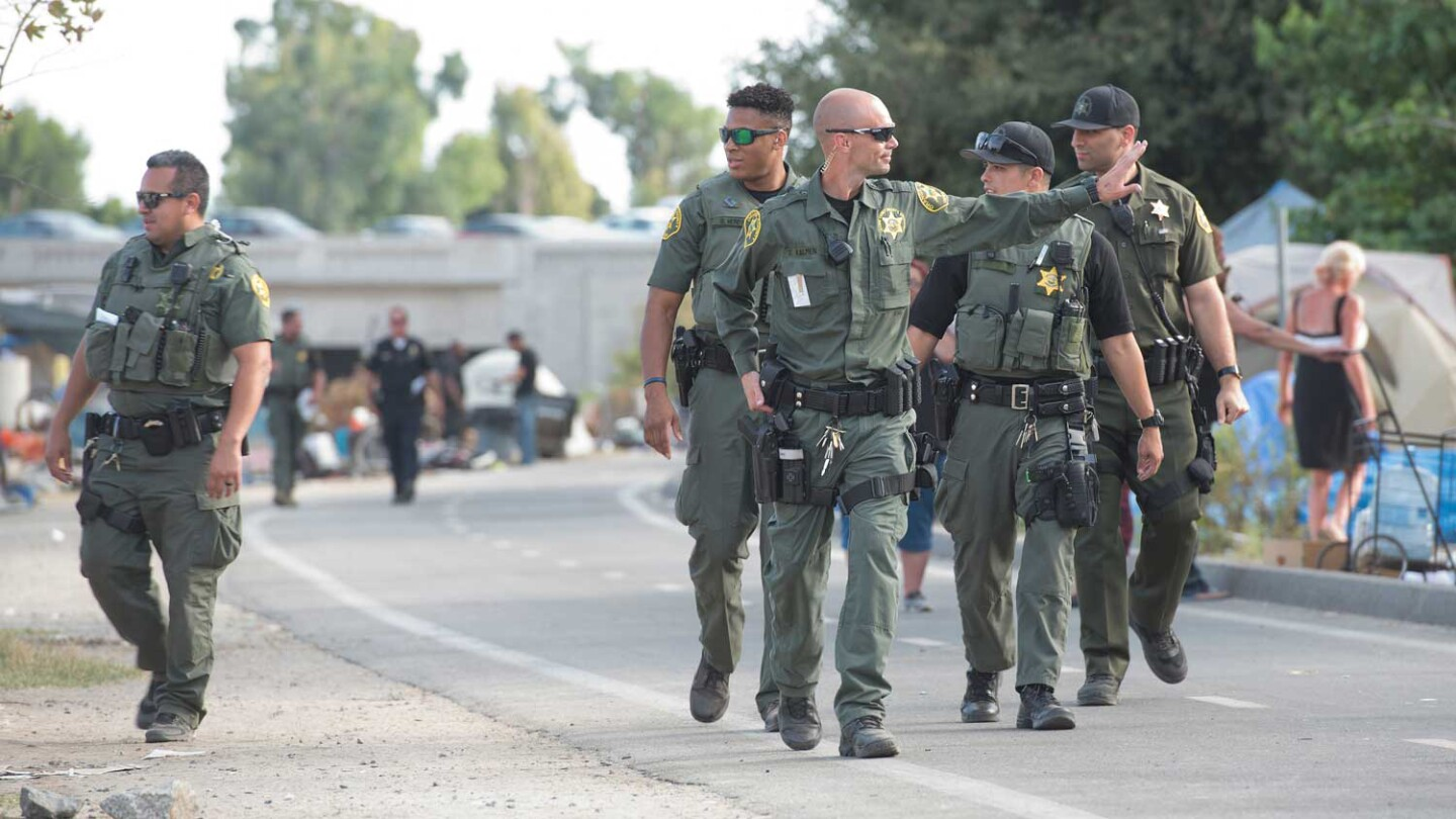 Orange County Sheriff's Deputies walk along Santa Ana Riverbed homeless camp
