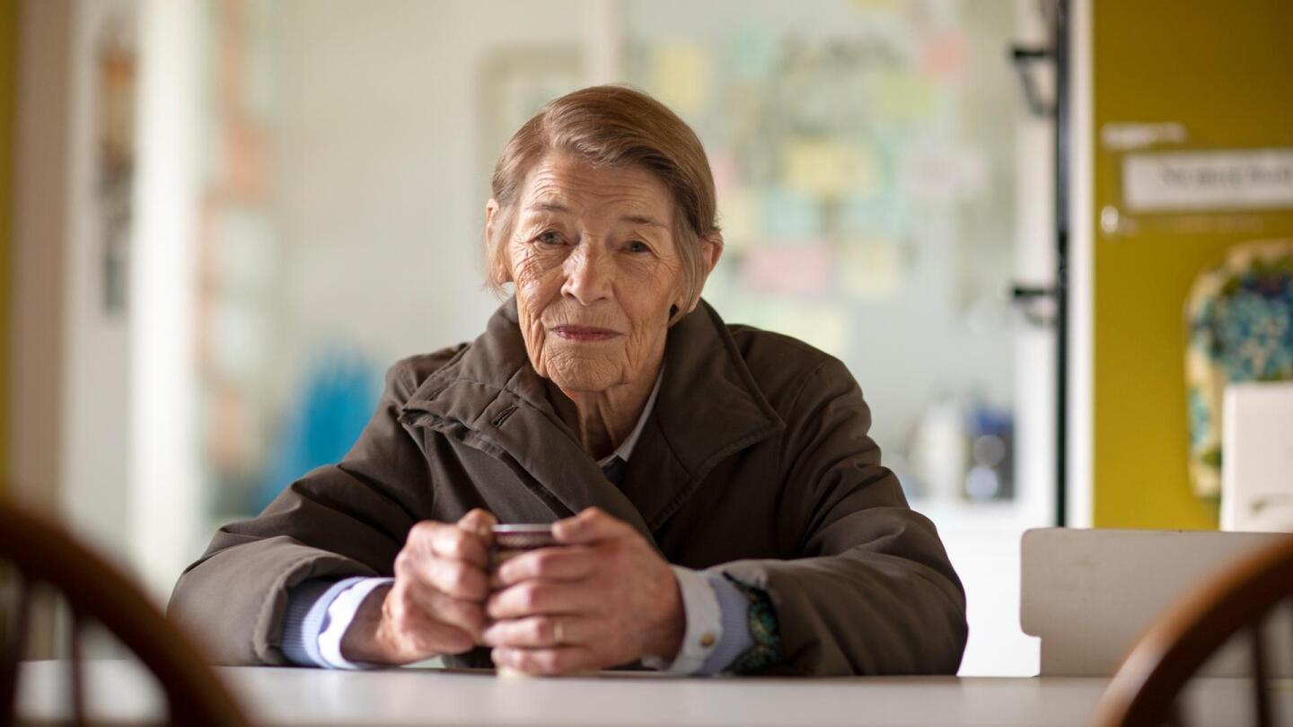 An elderly woman sits with mug in hand at a dining table.