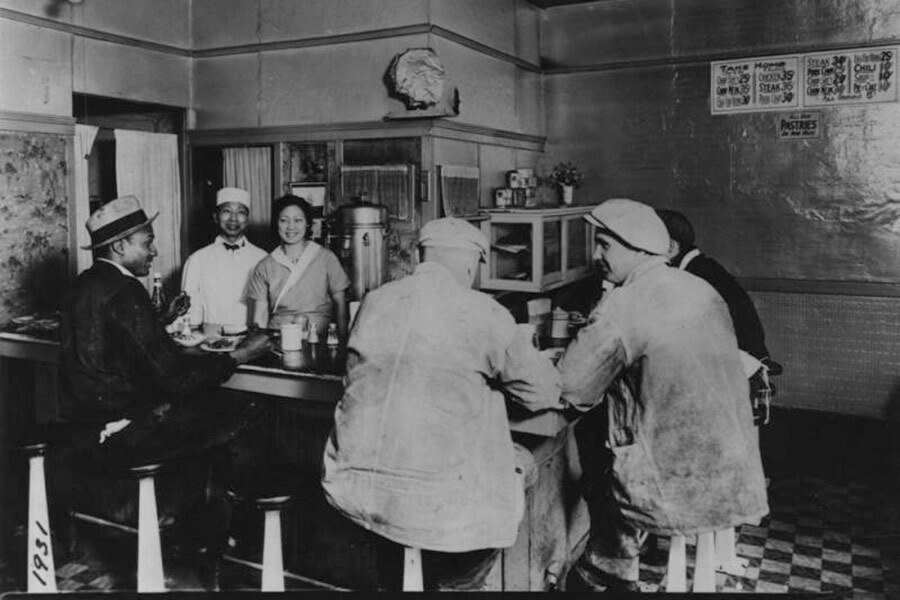 Black and white photo of a Korean American couple standing behind the counter at their restaurant serving customers, 1932